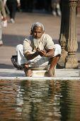 Old man performing ablution at Jama Masjid, Delhi, India