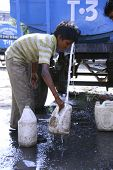 DELHI, INDIA - SEPTEMBER 22 : A young boy collects drinking water during water shortage on September