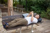 Serious Young Student Lying On Bench And Using Mobile Phone. Portrait Of Latin American Businessman  poster