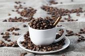 Whole Browned To Dark Brown Coffee Beans On A Linen Tablecloth poster