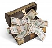 An old wooden trunk filled with UAE Dirhams.