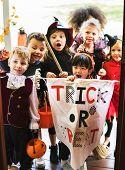 Little children trick or treating on Halloween poster