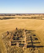 Drone Photo Of The Ruins Of An Old House In Countryside Fields poster