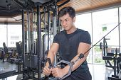 Determined Asian Man Exercising Pecs On Gym Equipment. Serious Guy With Gym Equipment In Background. poster