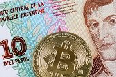 A Macro Image Of A Golden Bitcoin With A Ten Peso Argentinian Bill In Macro poster
