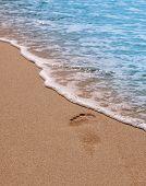 Human footprints on the beach. Sand and sea wave.