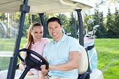 image of caddy  - Young couple in a golf car - JPG