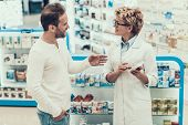 Woman Pharmacist Counseling Customer In Drugstore. Mature Pharmacist Wearing White Coat And Glasses  poster