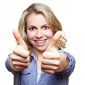 Smiling attractive woman holding her two thumbs up