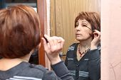 Mature Caucasian Woman Applying Make Up Against Mirror In Domestic Room poster