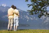 Couple Arm In Arm At A Mountain Lake