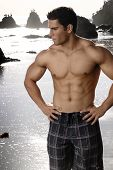 stock photo of fitness man body  - Young sexy shirtless bodybuilder on the beach - JPG