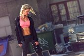 stock photo of kettlebell  - Attractive and athletic woman with kettlebell exercising outdoors - JPG