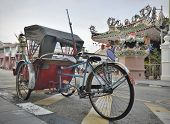 stock photo of tricycle  - Traditional tricycle in street with the Yap Kongsi chinese temple and traditional shophouses in background Georgetown - JPG