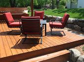 stock photo of red siding  - Backyard deck design with furniture on freshly stained deck - JPG