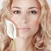 Closeup portrait of cute girl with blond curly hair holding gentle white calla flower, enjoying day