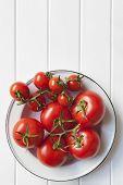 Rebe Tomaten in rustikalen Emaille Schüssel über weiße Holz.  Viele Textfreiraum.