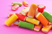 closeup of a pile of liquorice candies of different colors, on a pink background