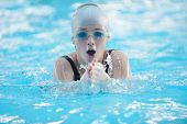 Happy muscular swimming woman  wearing glasses and cap at swim pool and represent health and fit con