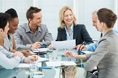 stock photo of coworkers  - Group Of Happy Coworkers Discussing In Conference Room - JPG