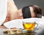 stock photo of blindfolded man  - Man with Sleeping mask sleep on a bed cup of herbal tea in the foreground - JPG