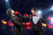 Two young businessman boxing againts dark background . conceptual collage