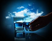Two glasses of blue liquid against cloudy background
