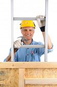 Closeup of  a carpenter climbing a ladder isolated over white. The man wearing a work shirt, jeans, gloves is holding a hammer and is partially hidden behind a wood framed wall. Vertical Format.
