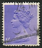 UK-CIRCA 1967: A stamp printed in UK shows image of Elizabeth II is the constitutional monarch of 16 sovereign states known as the Commonwealth realms, in purple, circa 1967.