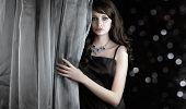 Bela mulher por trás da cortina em fundo escuro cintilante