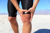 Injuries - sports running knee injury on man. Male runner with pain, maybe from sprain knee. Close u
