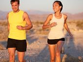 Fitness sport couple running jogging outside laughing happy training together outdoors. Runners in cross country run on trail outside. Happy multiethnic young couple, Caucasian man, Asian woman.