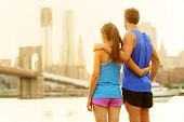 Fitness couple relaxing after running in Brooklyn, New York City, USA. Happy sporty fit young interracial couple enjoying view of Brooklyn Bridge after jogging training outside. Woman and man in 20s.