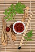 Chinese herbal medicine of saffron spice and angelica herb root with leaf sprigs over bamboo backgro