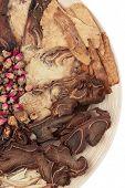 Seleção de Fitoterapia tradicional chinesa em uma tigela de madeira sobre o fundo branco.