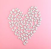 Puzzle made heart shape on pink background