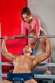 Female trainer helping guy to train in the gym Bar Bench Press