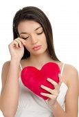 stock photo of loveless  - Beautiful upset brunette girl crying and holding a red heart - JPG