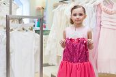 Beautiful girl tries on a festive red dress in the store childrens clothes
