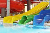 Pool with clear water and multi-colored water slides in indoor aquapark.