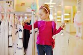 Little girl with rucksack on shoulders looks over dresses hanging on stand in clothing store