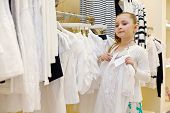stock photo of blouse  - Little girl tries on white blouse in clothing store - JPG