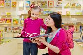 Mother shows to daughter big fold-out book in book department of store