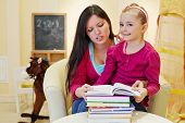 Mother reads book to her daughter sitting at table in armchair in playroom