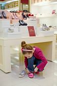 Little girl going to try on new shoes in store