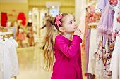 Little girl looks with interest, touching chin with fingers, upon dresses hanging at stand in clothing store