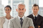 Businessman standing with colleagues behind with arms crossed