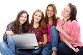 Happy teen girls learning with notebook, over white