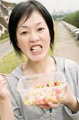 Mature Asian woman eat salad in outdoor park in daytime.