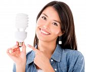 Woman holding an energy saving lightbulb - isolated over white